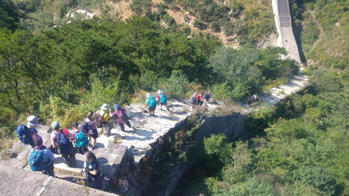 Group of trekkers walking down steep steps of Great Wall
