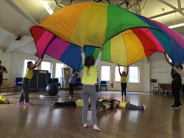 Brownies playing a game with a parachute for International Women's Day