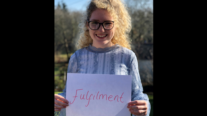 Young woman holding hand written sign that says fulfilment